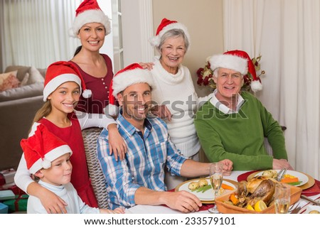 Happy extended family in santa hat looking at camera at home in the living room - stock photo
