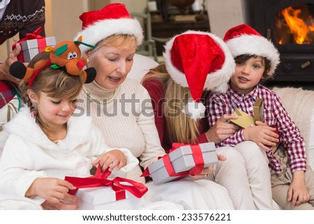 Happy extended family opening gifts on the couch at home in the living room