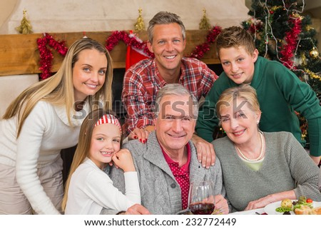 Happy extended family posing at christmas time at home in the living room - stock photo