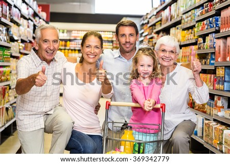 Happy extended family showing thumbs up at the supermarket - stock photo