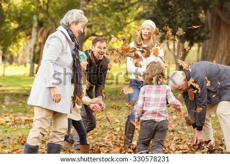 Happy extended family throwing leaves around on an autumns day - stock photo