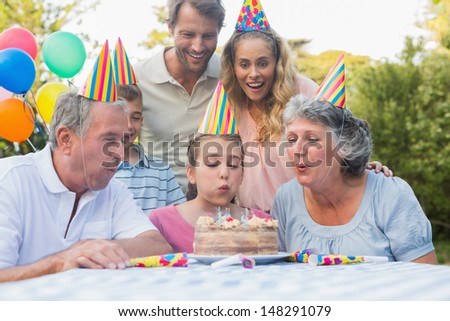 Happy extended family watching girl blowing out birthday candles at picnic table outside - stock photo