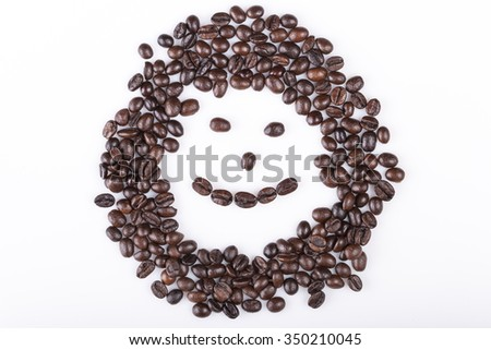 Happy face made of coffee beans on a white background - stock photo