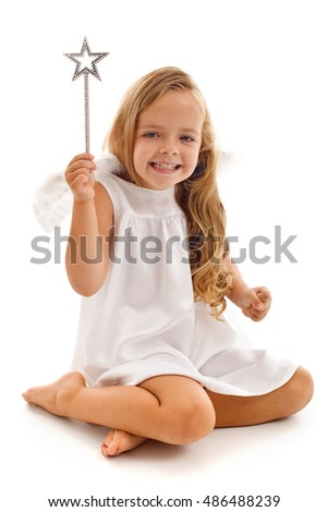 Happy fairy doing her magic - little girl waving a star shaped wand