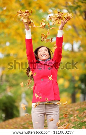 Happy fall woman throwing autumn leaves up in the air smiling blissful and cheerful in autumn forest. Young beautiful multicultural Caucasian / Asian woman model outside. - stock photo