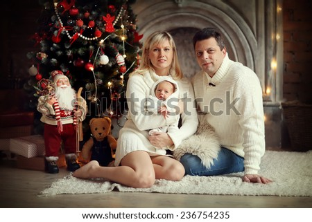 Happy family: a beautiful young blonde woman and her smiling husband in white clothes sitting on floor and holding their cute newborn baby against a decorated twinkling Christmas tree. New Year's Eve. - stock photo