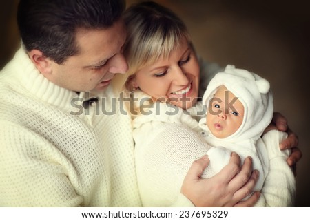 Happy family: a close up portrait of a beautiful young blonde woman and her smiling husband in white clothes holding their cute newborn baby - stock photo