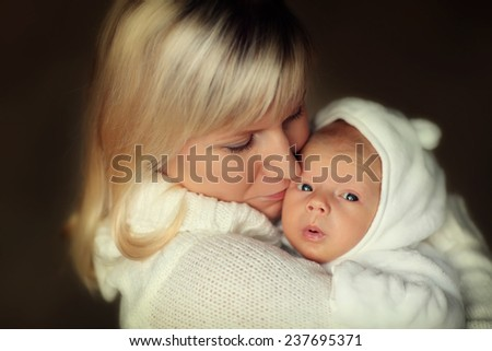 Happy family: a close up portrait of a beautiful young blonde woman in white clothes holding her cute newborn baby in a white suit and kissing him. - stock photo