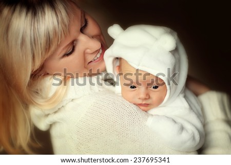 Happy family: a close up portrait of a beautiful young smiling blonde woman in white clothes holding her cute newborn baby in a white suit. - stock photo