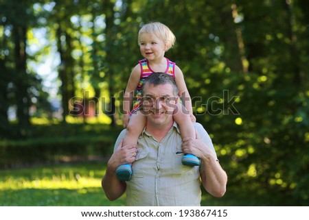 Happy family, a father and his daughter, cute toddler girl with blonde curly hair, enjoying time outdoors, hugging and kissing, on a sunny summer day - stock photo