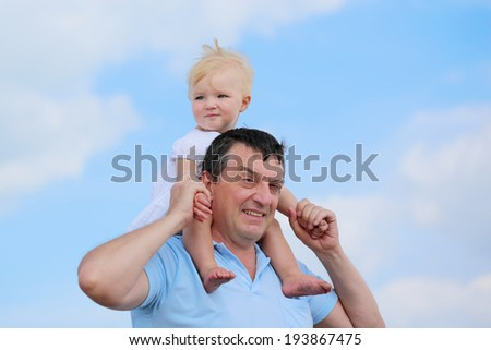 Happy family, a father and his daughter, cute toddler girl with blonde curly hair, enjoying time outdoors, hugging and kissing, on a sunny summer day - blue sky with white clouds at the background - stock photo