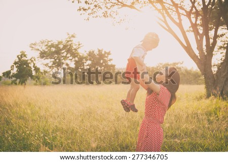 Happy family. A mother and son playing in grass fields outdoors at evening.Vintage Tone and copy space. - stock photo