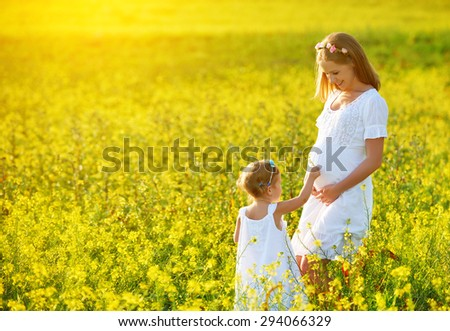 happy family, a pregnant mother and daughter little girl child in the summer  meadow with yellow flowers - stock photo