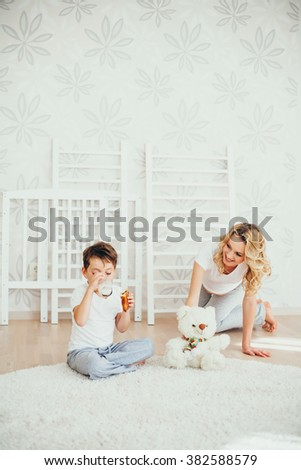 happy family.a pregnant woman.interior.milk. cheerful women. enjoyment. mather playing, with son - stock photo