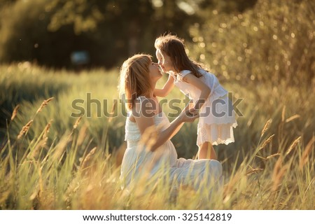 Happy family: a young beautiful pregnant woman and her little cute daughter walking together in the meadow on a sunny summer day. Nature in the country. Relationship between parents and children. - stock photo