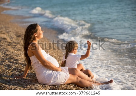 Happy family: a young beautiful pregnant woman with her little cute daughter walking near the sea on a sunny summer day. Parents and kids relationship. - stock photo