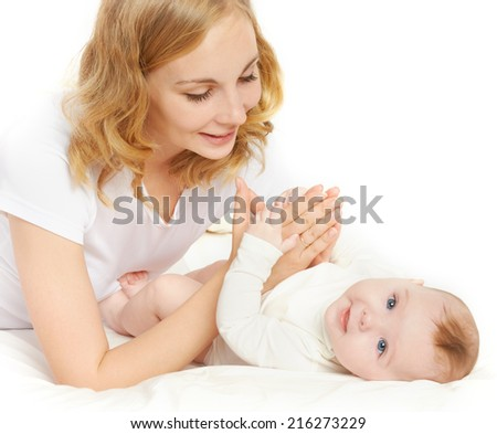 happy family. a young mother playing with her baby in bed - stock photo