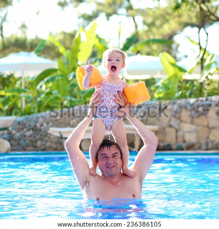 Happy family, active father with little child, adorable toddler girl, having fun together in outdoors swimming pool in water park during sunny summer sea vacation in tropical resort - stock photo