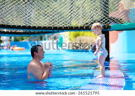 Happy family, active father with little child, adorable toddler girl, having fun together in outdoors swimming pool in water park during sunny summer sea vacation in tropical resort. Focus on kid - stock photo