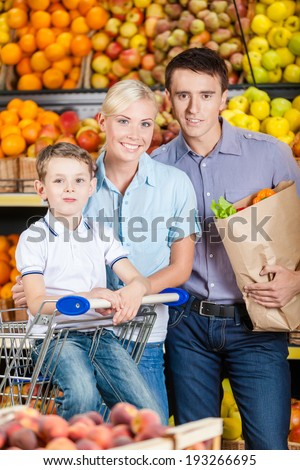 Happy family against shelves of fruits goes shopping. Father keeps a packet with fruits and son sits in the cart - stock photo