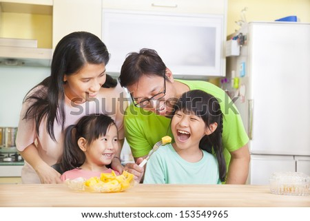 happy family and daughter eating fruits in the kitchen