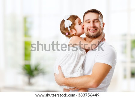 happy family and father's day. child daughter kissing and hugging dad