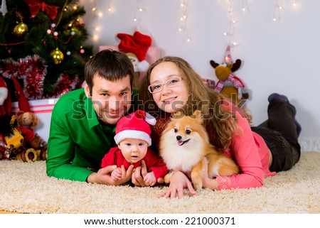 Happy family and the dog spending Christmas time at home laying on the carpet near the Christmas tree. - stock photo