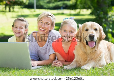 Happy family and their dog smiling at the camera on a sunny day - stock photo