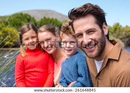 Happy family at a lake in the countryside - stock photo