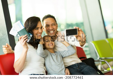 happy family at airport taking self portrait with smart phone at airport - stock photo