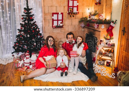 happy family at Christmas and New Year with gifts around the Christmas tree. in Christmas red hat in red clothes - stock photo