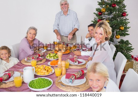 Happy family at christmas dinner with grandfather carving the turkey - stock photo