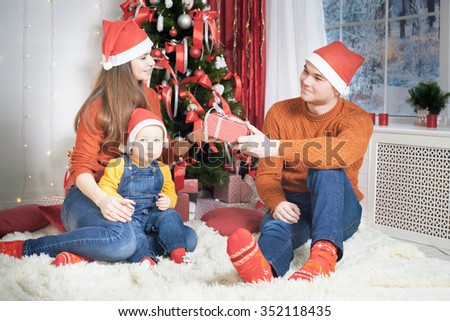 Happy family at Christmas eve sitting together near decorated tree at living room, home. Father giving gift to mother and boy looking at camera. Concept of celebrating New Year holiday at Russia - stock photo