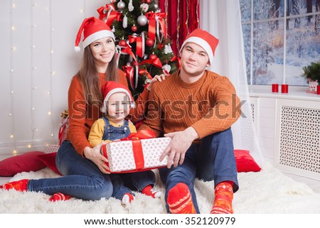 Happy family at Christmas eve sitting together near decorated tree at living room, home. Father giving gift to baby and mother looking at child. Concept of celebrating New Year holiday at Russia - stock photo