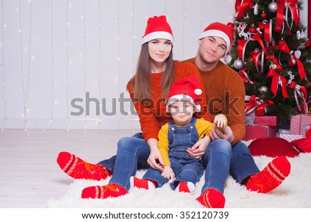 Happy family at Christmas eve sitting together near decorated tree at living room, home. They dressed in winter pullover and Santa hat. Father, mother and boy looking at camera. New Year. - stock photo