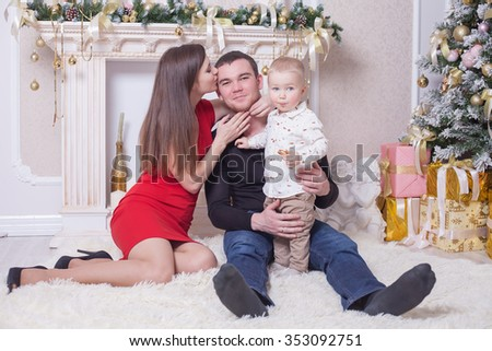 Happy family at Christmas eve sitting together near fireplace and decorated tree at living room, home. Concept of celebrating New Year holiday at Russia. Father, mother and boy looking at camera. - stock photo