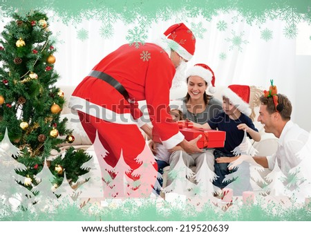 Happy family at christmas evening at home against green snowflake design - stock photo