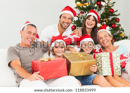 Happy family at christmas holding gifts on the couch - stock photo