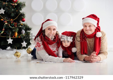Happy family at Christmas. The parents and the baby lying on the floor and smiling. In public, the red caps of Santa. In the background stands and Christmas tree ornaments. - stock photo