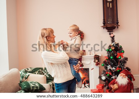 Happy family at christmas time. Mother with her son in cozy sweaters in living room with xmas decorations