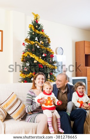 Happy family at Christmas time on sofa  in living room - stock photo