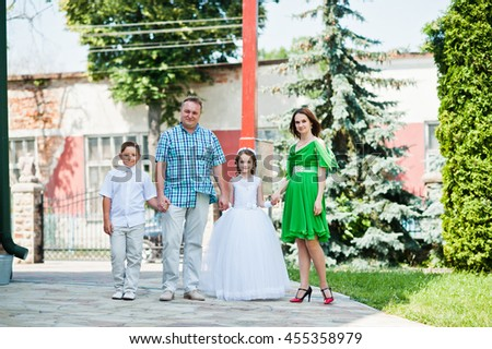 Happy family at first holy communion walking background church cross