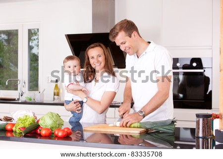 Happy family at home in the kitchen cooking, making a meal - stock photo