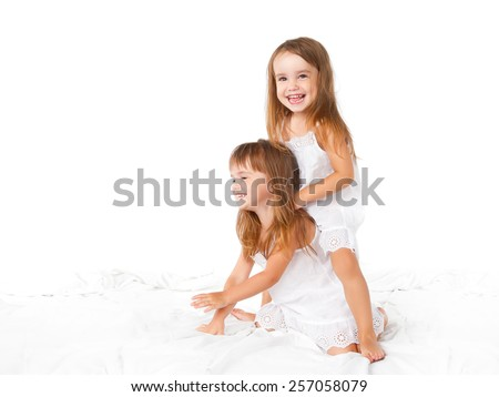 happy family at home. kids twin sisters jumping on the bed, playing and laughing - stock photo