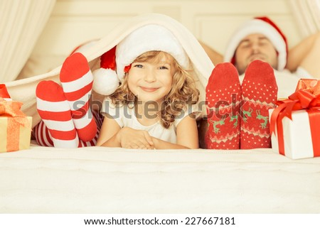 Happy family at home. Mother, father and child with Christmas gift. Winter holiday concept - stock photo