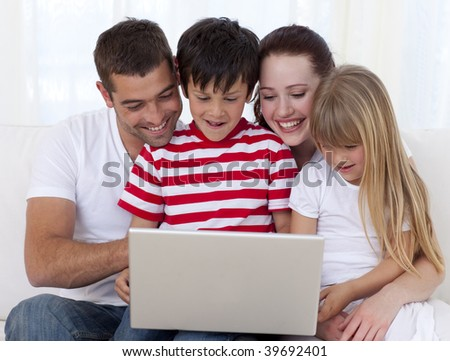Happy family at home playing with a laptop