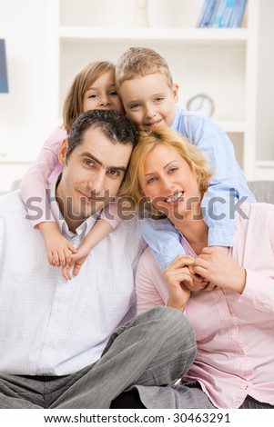 Happy family at home with daugther and son, smiling. Children hugging their parents from behind