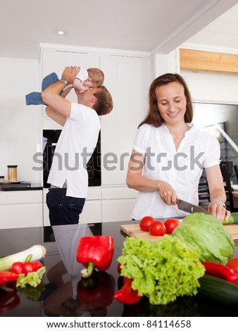 Happy family at home with mother making salad and father playing with son in background - stock photo