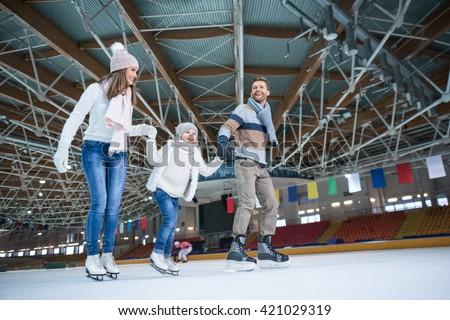 Happy family at skating rink - stock photo
