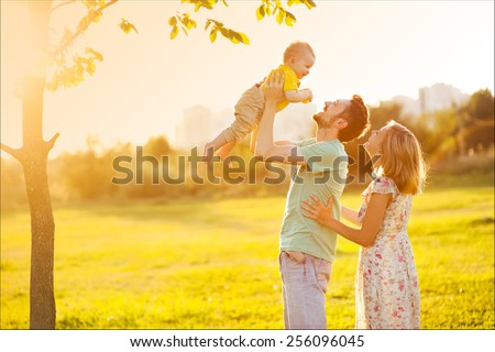 Happy family at sunset - stock photo